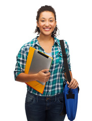 smiling student with folders, tablet pc and bag