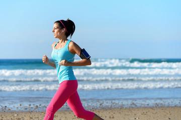 Woman running on beach with earphones