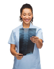 smiling female doctor or nurse looking at x-ray