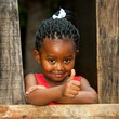 Little african girl at wooden fence with thumbs up.
