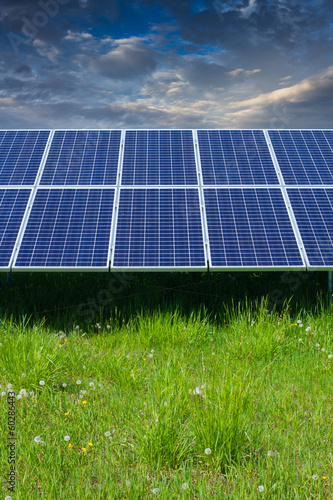 solar photovoltaic cell panels on green grass under cloudy sky