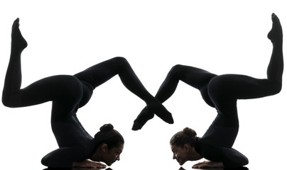 two women contortionist  exercising gymnastic yoga silhouette