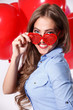 Portrait of a beautiful young woman with heart-shaped eyeglasses