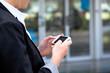 Frau schreibt eine SMS mit ihrem Handy