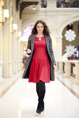 Young beautiful woman in red dress walks in the store