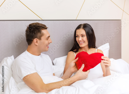 smiling couple in bed with red heart shape pillow