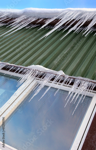 Many icicles hang on chalet´s roof