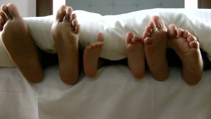 family feet under the sheet