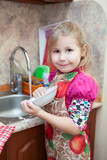 Girl in the kitchen with a plate in his hand at the sink