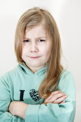 Young girl with an angry look and crossed arms