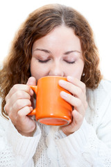 Young woman drinking from orange mug, isolated on white