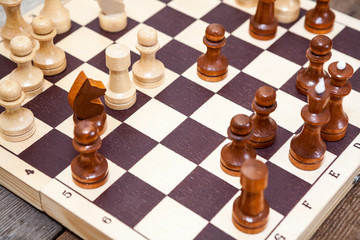 Close up view of chess pieces on wooden board table