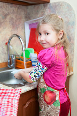 Caucasian pretty young girl in the kitchen washing dishes