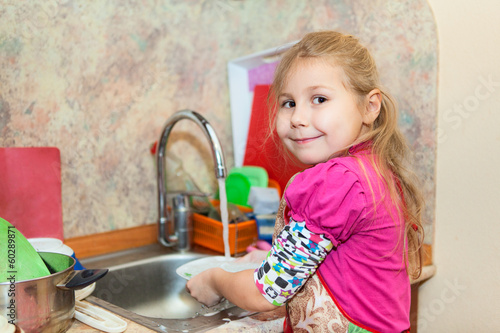 Small girl in the kitchen washing dishes, copyspace