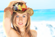 Beautiful blond happy woman, holding her summer hat on the beach