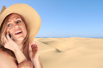 Blond woman in a summer hat talking on a phone