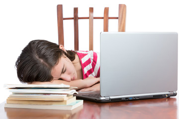 Tired teen student sleeping on her desk isolated on white