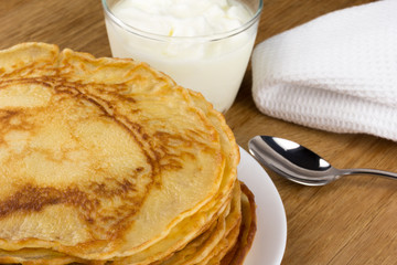 pancakes on a plate with a cup of sour cream