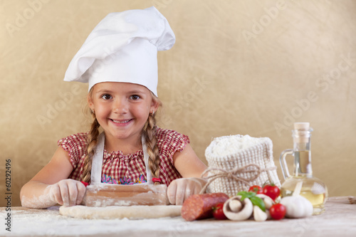 Happy chef little girl stretching the dough