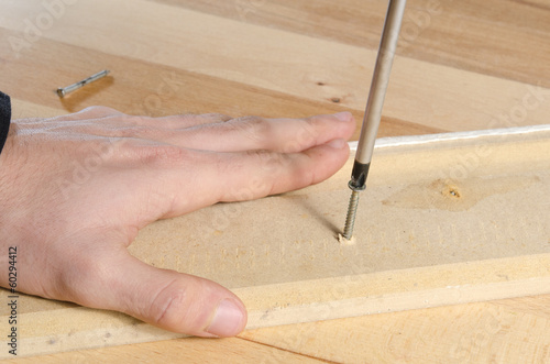 Closeup of carpenter tightening a screw with a screwdriver