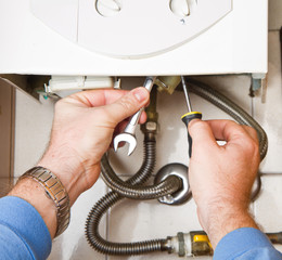 Plumber at work. Servicing gas boiler
