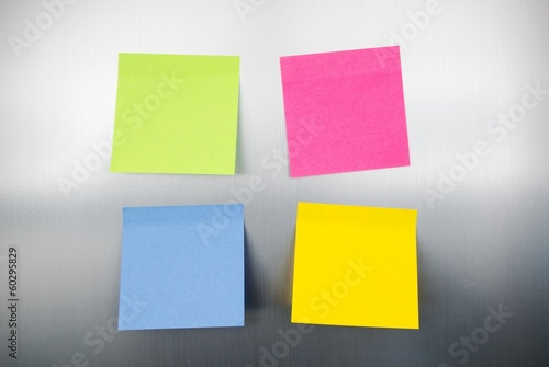 Close up of coloured reminders on fridge. Metallic background wi