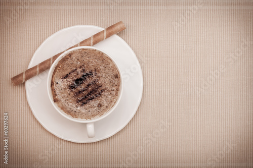 White cup coffe and waffle roll with cream on brown background