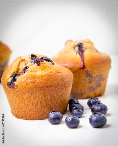 Couples of blueberry muffins on white background