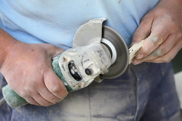 construction worker using an angle grinder cutting tile