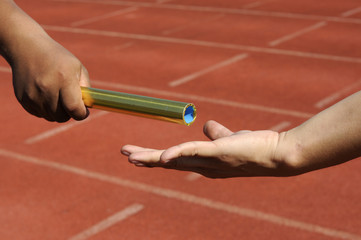 Relay-athletes hands sending action.