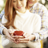 young loving couple holding heart-shaped gift box