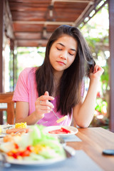 Teen girl eating breakfast on outdoor veranda