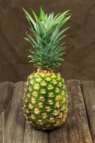 Ripe pineapple on wooden table.
