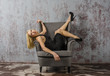 Cheerful young blonde woman in black dress in a chair tumbles