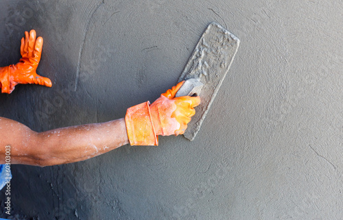 Staande foto Industrial geb. plasterer concrete worker at wall of house construction