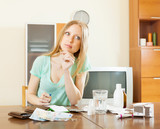 serious  blonde woman with medications and money