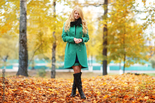 sad melancholy blond woman in autumn forest