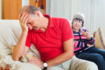 Sad mature man listening to angry wife