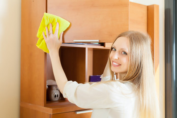 Cheerful  woman wiping the dust from wooden furniture