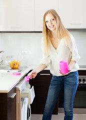 long-haired woman putting whitener in to washing machine