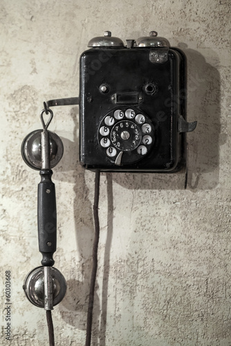 Vintage black phone hanging on old gray concrete wall