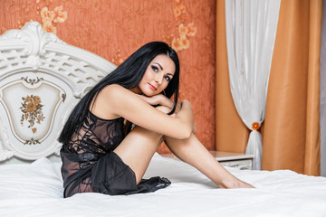 Attractive brunette woman on bed