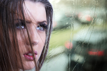 Cute girl by rainy window in bad weather