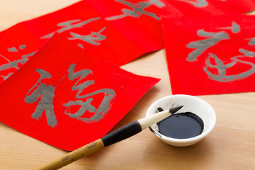 Writing Chinese calligraphy for Chinese new year, word Fu, mean