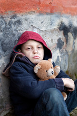 homeless boy leaned against the wall with bear