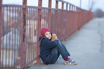 homeless boy sitting on the bridge