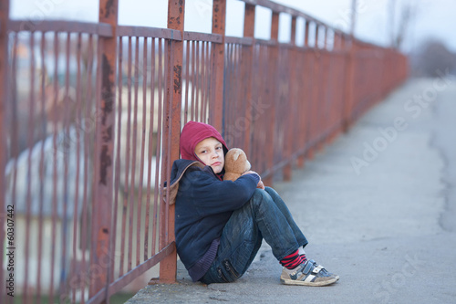 homeless boy sitting on the bridge
