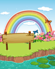 An empty wooden signboard at the riverbank and a rainbow in the