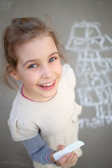 A smiling girl standing next to a hopscotch