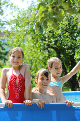 Three happy kids having fun in swimming pool on the courtyard